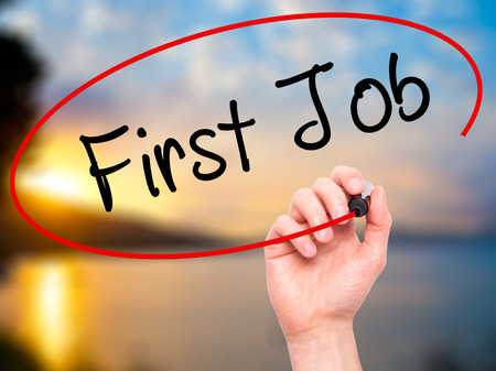 apprenticeship employee: Man Hand writing First Job with black marker on visual screen. Isolated on nature. Business, technology, internet concept. Stock Photo