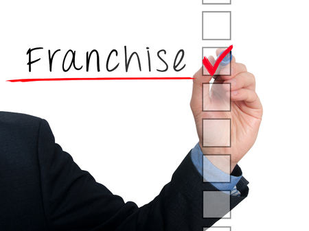 stock listing: Businessman hand writing Franchise and check listing task. Isolated on white background. Stock photo