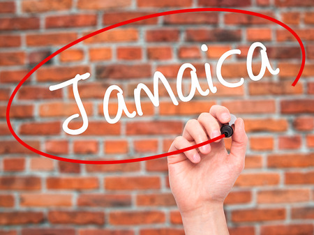 bob: Man Hand writing Jamaica  with black marker on visual screen. Isolated on bricks. Business, technology, internet concept. Stock Photo