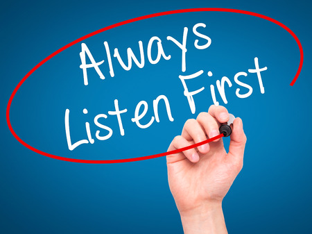 always listen first: Man Hand writing Always Listen First with black marker on visual screen. Isolated on blue. Business, technology, internet concept. Stock Photo