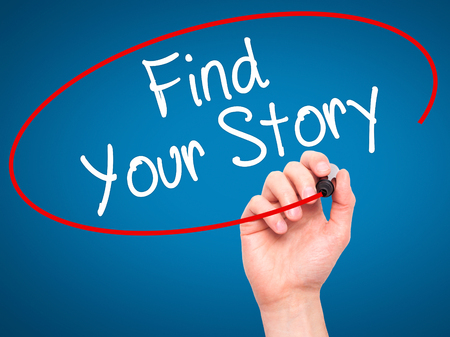 photo story: Man Hand writing Find Your Story with black marker on visual screen. Isolated on blue. Business, technology, internet concept. Stock Photo