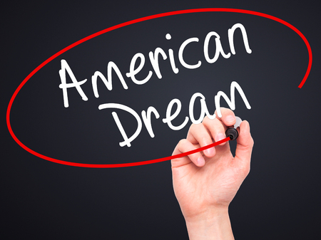 american dream: Man Hand writing American Dream with black marker on visual screen. Isolated on black. Business, technology, internet concept. Stock Image