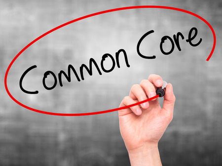 repeal: Man Hand writing Common Core with black marker on visual screen. Isolated on grey. Education, technology, internet concept. Stock Image