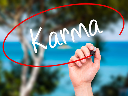 downfall: Man Hand writing Karma  with black marker on visual screen. Isolated on background. Business, technology, internet concept. Stock Photo