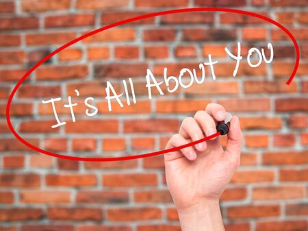 about you: Man Hand writing Its All About You with black marker on visual screen. Isolated on bricks. Business, technology, internet concept. Stock Photo
