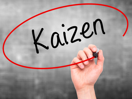 Man Hand writing Kaizen with black marker on visual screen. Isolated on grey. Business, technology, internet concept. Stock Photo