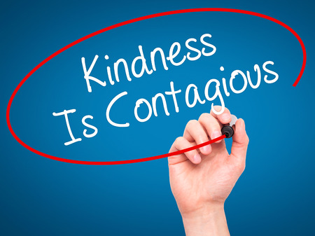 Man Hand writing Kindness Is Contagious with black marker on visual screen. Isolated on background. Business, technology, internet concept. Stock Photo Archivio Fotografico