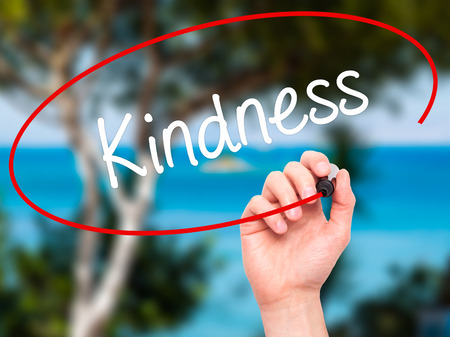 solicitude: Man Hand writing Kindness with black marker on visual screen. Isolated on nature. Business, technology, internet concept. Stock Photo
