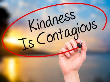 pobreza: Escritura de la mano del hombre la bondad es contagiosa con marcador negro en la pantalla visual. Aislado en el fondo. Negocios, la tecnología, el concepto de internet. Foto de stock Foto de archivo