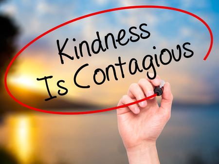poverty: Man Hand writing Kindness Is Contagious with black marker on visual screen. Isolated on background. Business, technology, internet concept. Stock Photo Stock Photo