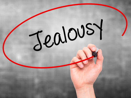 envious: Man Hand writing Jealousy with black marker on visual screen. Isolated on grey. Business, technology, internet concept. Stock Photo