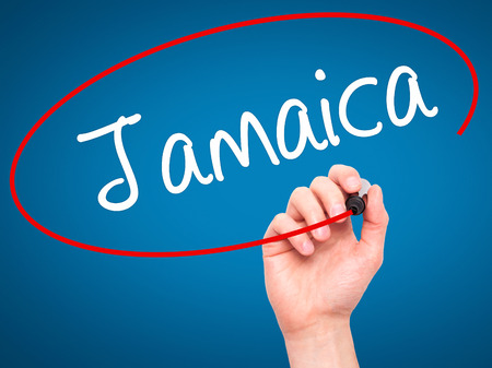 bob: Man Hand writing Jamaica  with black marker on visual screen. Isolated on blue. Business, technology, internet concept. Stock Photo Stock Photo