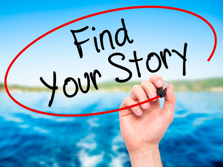 photo story: Man Hand writing Find Your Story with black marker on visual screen. Isolated on nature. Business, technology, internet concept. Stock Photo