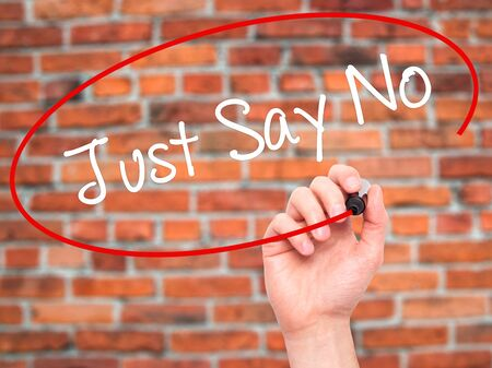 Man Hand writing Just Say No with black marker on visual screen. Isolated on bricks. Business, technology, internet concept. Stock Photo