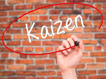 kaizen: Man Hand writing Kaizen with black marker on visual screen. Isolated on bricks. Business, technology, internet concept. Stock Photo
