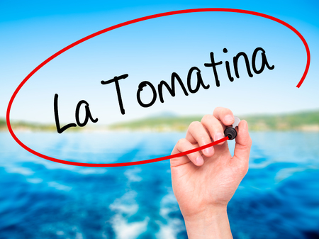 fiesta popular: Man Hand writing La Tomatina with black marker on visual screen. Isolated on nature. Business, technology, internet concept.
