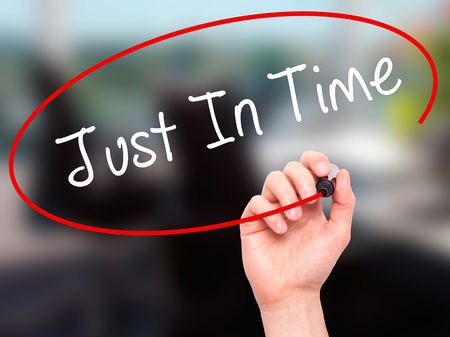 eliminating: Man Hand writing Just In Time with black marker on visual screen. Isolated on office. Business, technology, internet concept. Stock Photo