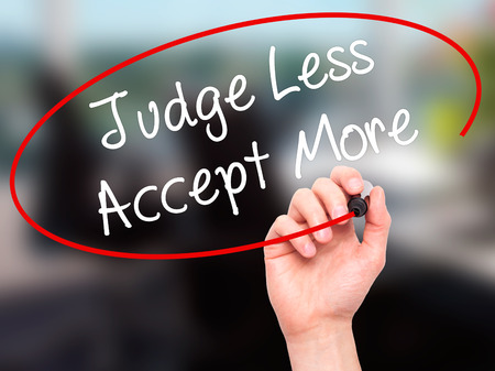 Man Hand writing Judge Less Accept More with black marker on visual screen. Isolated on background. Business, technology, internet concept. Stock Photo