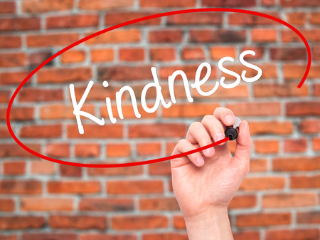 solicitude: Man Hand writing Kindness with black marker on visual screen. Isolated on bricks. Business, technology, internet concept. Stock Photo