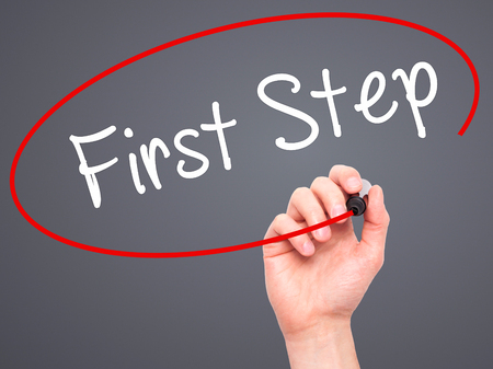 first step: Man Hand writing First Step  with black marker on visual screen. Isolated on grey. Business, technology, internet concept. Stock Photo