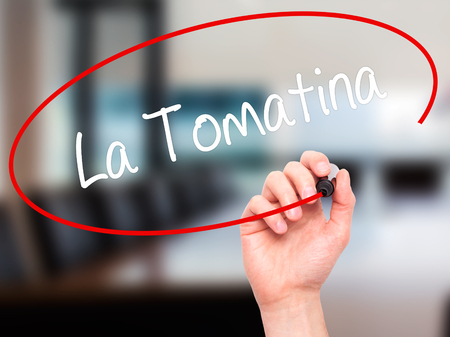 fiesta popular: Man Hand writing La Tomatina with black marker on visual screen. Isolated on office. Business, technology, internet concept. Stock Photo