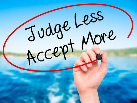 hostility: Man Hand writing Judge Less Accept More with black marker on visual screen. Isolated on background. Business, technology, internet concept. Stock Photo