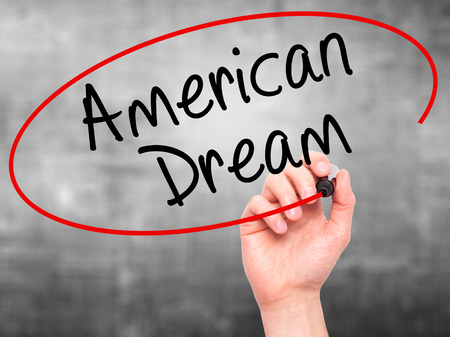 ethos: Man Hand writing American Dream with black marker on visual screen. Isolated on grey. Business, technology, internet concept. Stock Image