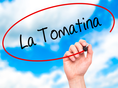 fiesta popular: Man Hand writing La Tomatina with black marker on visual screen. Isolated on sky. Business, technology, internet concept.