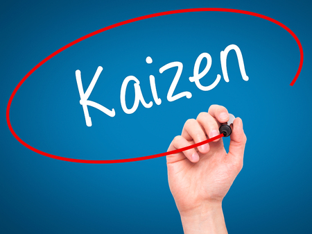 kaizen: Man Hand writing Kaizen with black marker on visual screen. Isolated on blue. Business, technology, internet concept. Stock Photo
