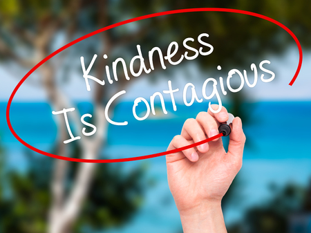 helpfulness: Man Hand writing Kindness Is Contagious with black marker on visual screen. Isolated on background. Business, technology, internet concept. Stock Photo Stock Photo