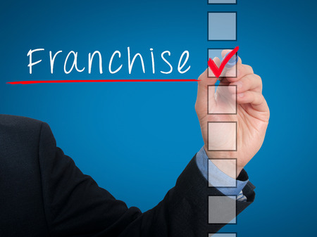 stock listing: Businessman hand writing Franchise and check listing task. Isolated on blue background. Stock photo Stock Photo