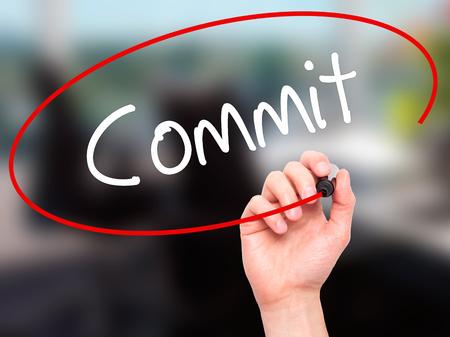 comité d entreprise: Man Hand Writing Commit avec un marqueur noir sur l'écran visuel. Isolé sur fond. Affaires, technologie, internet concept. photo Banque d'images