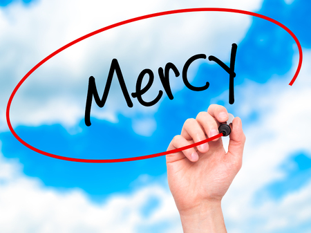 personal god: Man Hand writing Mercy with black marker on visual screen. Isolated on sky. Business, technology, internet concept. Stock Photo