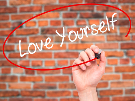 egoistic: Man Hand writing Love Yourself with black marker on visual screen. Isolated on bricks. Business, technology, internet concept. Stock Photo