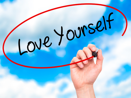egoistic: Man Hand writing Love Yourself with black marker on visual screen. Isolated on sky. Business, technology, internet concept. Stock Photo Stock Photo