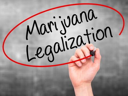 legislators: Man Hand writing Marijuana Legalization with black marker on visual screen. Isolated on grey. Live, technology, internet concept. Stock Photo