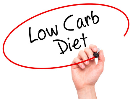 low carb diet: Man Hand writing Low Carb Diet with black marker on visual screen. Isolated on white. Business, technology, internet concept. Stock Photo