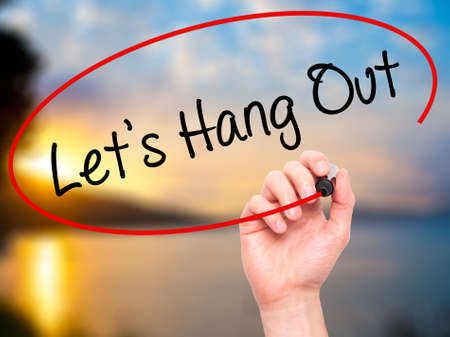 hang out: Man Hand writing Lets Hang Out with black marker on visual screen. Isolated on background. Business, technology, internet concept. Stock Photo