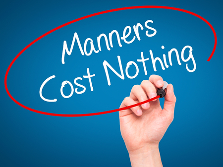 bad manners: Man Hand writing Manners Cost Nothing with black marker on visual screen. Isolated on blue. Business, technology, internet concept. Stock Photo Stock Photo