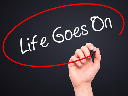 Man Hand writing Life Goes On with black marker on visual screen. Isolated on black. Business, technology, internet concept. Stock Photo