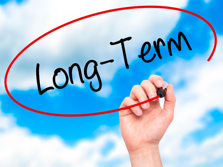 Man Hand writing Long-Term with black marker on visual screen. Isolated on sky. Business, technology, internet concept. Stock Photo Stock Photo