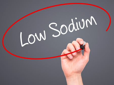 sodium: Man Hand writing Low Sodium with black marker on visual screen. Isolated on background. Business, technology, internet concept. Stock Photo Stock Photo