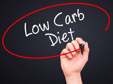 low carb diet: Man Hand writing Low Carb Diet with black marker on visual screen. Isolated on black. Business, technology, internet concept. Stock Photo