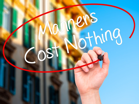 manners: Man Hand writing Manners Cost Nothing with black marker on visual screen. Isolated on city. Business, technology, internet concept. Stock Photo