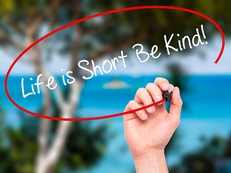 likable: Man Hand writing Life is Short Be Kind! with black marker on visual screen. Isolated on nature. Business, technology, internet concept. Stock Photo