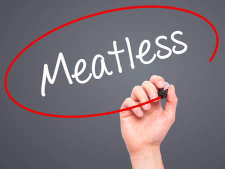 meatless: Man Hand writing Meatless  with black marker on visual screen. Isolated on grey. Business, technology, internet concept. Stock Photo Stock Photo