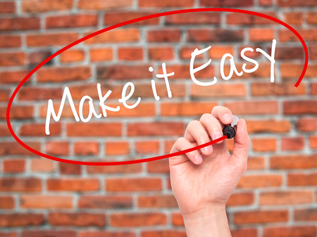 aftersales: Man Hand writing Make it Easy with black marker on visual screen. Isolated on bricks. Business, technology, internet concept. Stock Photo