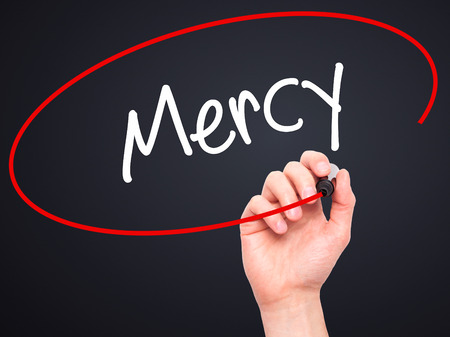 personal god: Man Hand writing Mercy with black marker on visual screen. Isolated on black. Business, technology, internet concept. Stock Photo Stock Photo