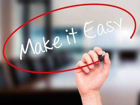 aftersales: Man Hand writing Make it Easy with black marker on visual screen. Isolated on office. Business, technology, internet concept. Stock Photo
