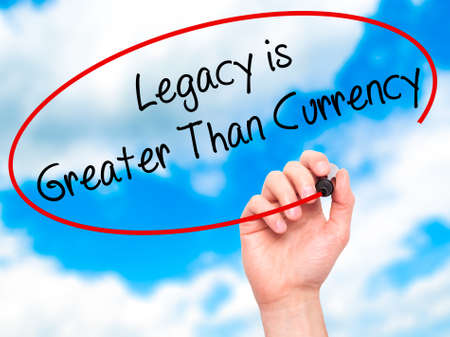 legacy: Man Hand writing Legacy is Greater Than Currency with black marker on visual screen. Isolated on background. Business, technology, internet concept. Stock Photo